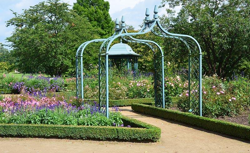 Hellblauer Gartenpavillon in formaler Buchsbaum Anlage