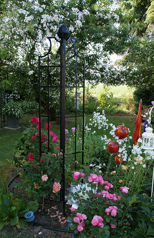 dreiflügeliger Obelisk im Blumenbeet