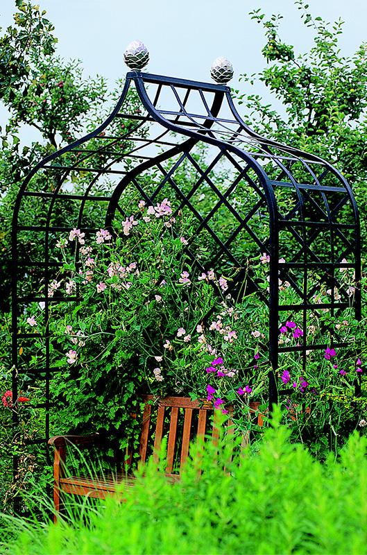 Rosenlaube im bewachsenen Garten mit Bank