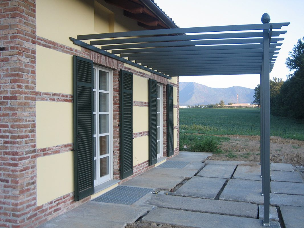 Grüne Pergola aus Metall an Hauswand