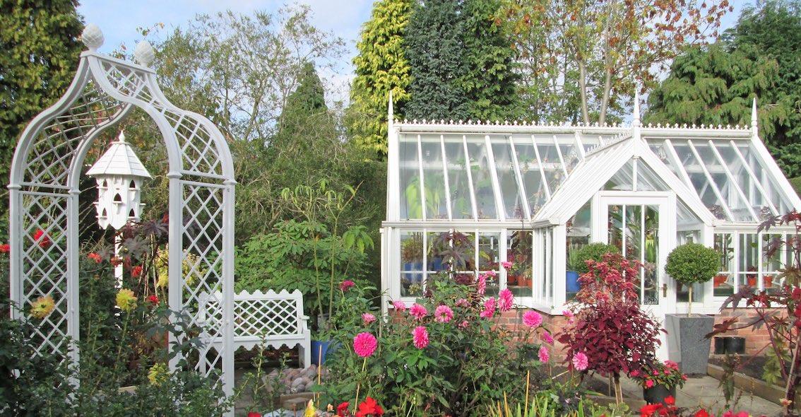 Weißer Metall Rosenbogen mit Parkbank und weißem Gewächshaus