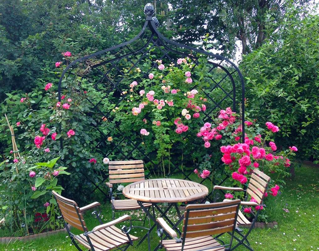 Gartensitzecke mit schwarzer breiter Metall Rosenlaube