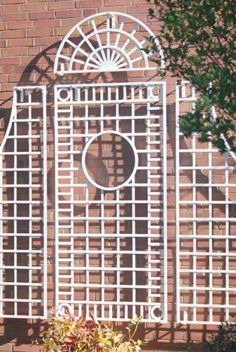 Gitterspalier aus Metall in weiss vor Klinkerwand