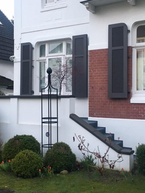 Klassischer Rosenobelisk vor Landhaus