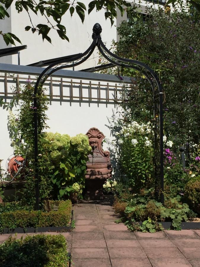 Massiver Metall Rosenbogen rahmt Blickachse zu Wandbrunnen