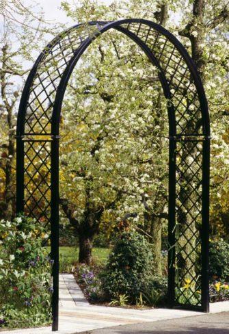 Metall Rosenbogen als Eingang in blühenden Obstgarten