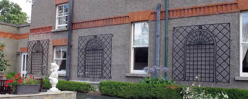 Metall Treillage Kombination zwischen Fenstern an grauer Hauswand