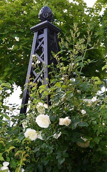Rosenpyramide aus Metall mit dicht gefüllten hell-cremefarbenen Rosenblüten