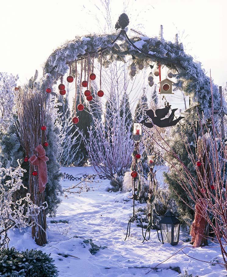 Rosenbogen im Winter mit roten Kugeln, Meisenknödeln, Blechkugel und Windlichter