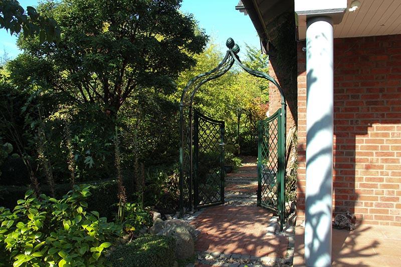 Klassischer Rosenbogen aus Metall mit Gartentor