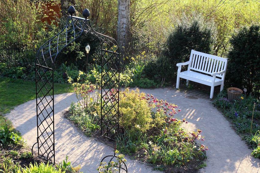 Rosenbogen Metall mit weißer Holzbank im Garten
