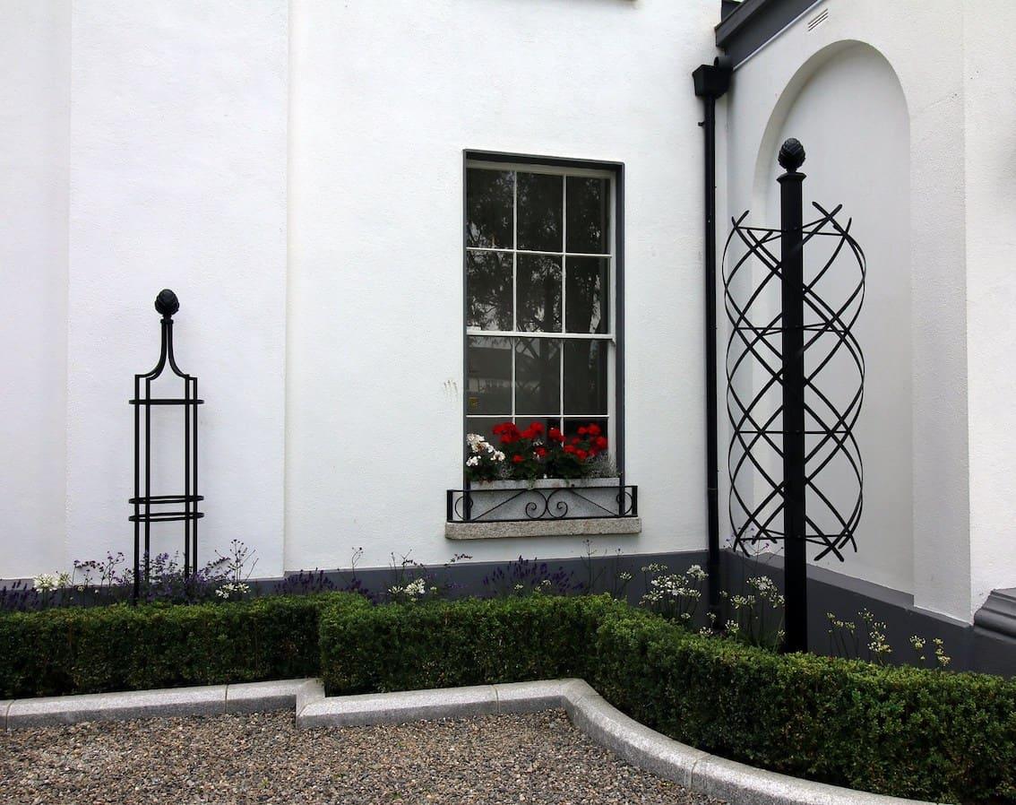 Zwei unterschiedliche schwarze Metall Rosensäulen vor weißer Villa