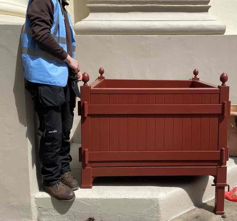 Roter großer massiver Metall Pflanzkübel auf Treppe